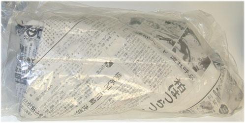 新聞紙にくるんでビニール袋に入ったカニ