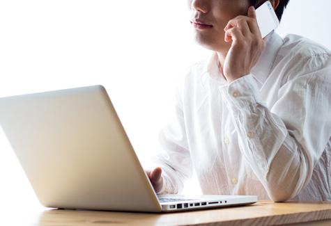 パソコンを見ながら電話する男性