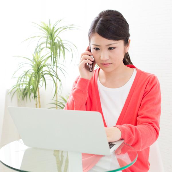 パソコンを見て電話する女性