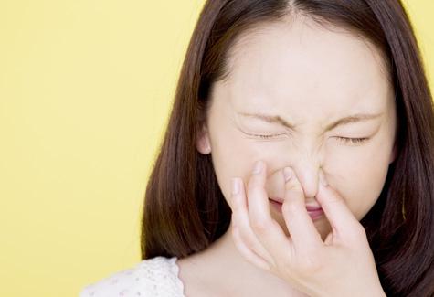 鼻をふさぐ女性